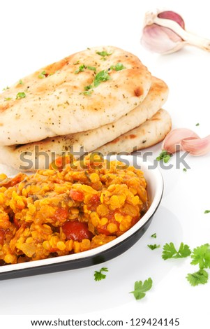 Delicious dal in bowl with naan flat bread and fresh herbs isolated on white background. Culinary eastern cuisine.