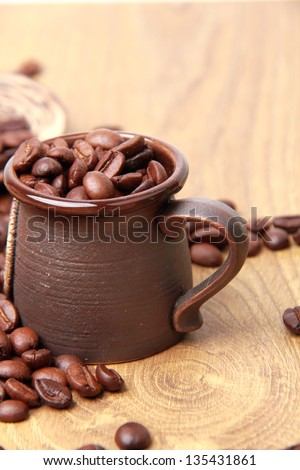 Delicious dark brown coffee beans in small ceramic coffee cup over textured background