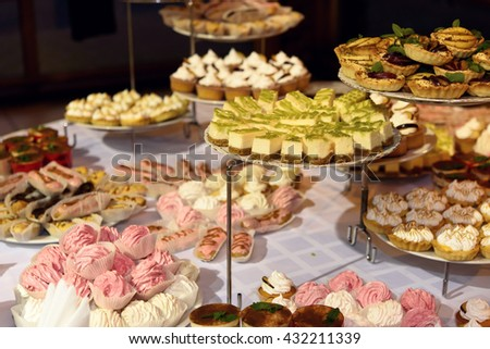 delicious decorated candy bar, sweets on tables for wedding reception, catering in restaurant - stock photo