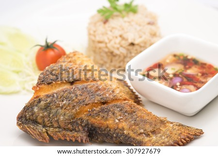 Delicious deep fried white bass or snapper fish with rice and chili sauce on white ceramic plate for food background  - stock photo