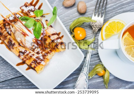 Delicious Dessert Eclair with Caramel and Ice Cream with a cup of tea on a wooden table - stock photo