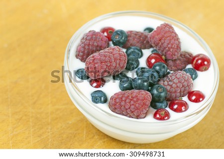 Delicious dessert made of yoghurt and ripe berries (raspberry, red currant and blueberry) - stock photo