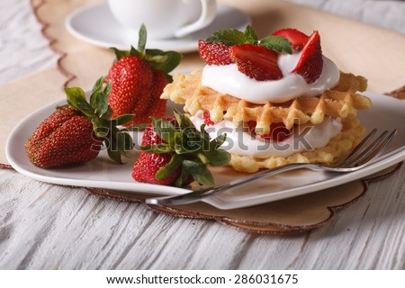 Delicious dessert: waffles with fresh strawberries and cream close-up on a plate. horizontal  - stock photo