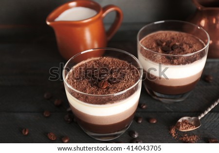 Delicious dessert with chocolate powder and coffee beans in glass - stock photo