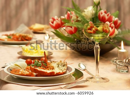 Delicious dinner table serving wine and lobster - stock photo
