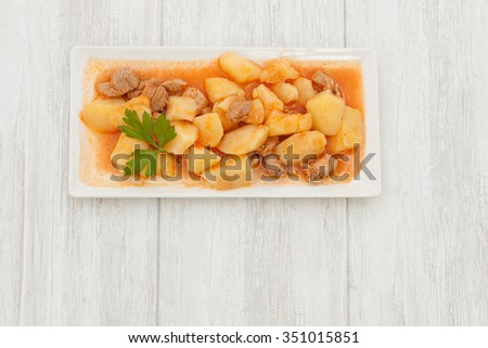 Delicious dish of cooked potatoes with meat on gray wooden background - stock photo