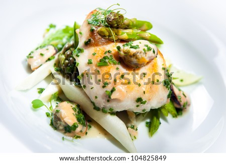 Delicious dish with fish fillet, asparagus and herbs on a plate - stock photo