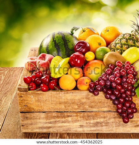 Delicious display of healthy fresh organic fruit in a wooden crate at farmers market with watermelon, grapes, orange, kiwi, peaches, apricot, cherry, lemon, pineapple and apples - stock photo