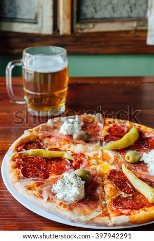 Delicious Domestic Pizza and Beer Mug on wooden table in a rustic restaurant. Ingredients peeled tomato, cheese, sausage, ham, sour cream, egg, pepperoni, olives, oregano. - stock photo
