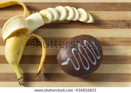 Delicious donut with banana and chocolate. Served on the wooden board. Decorated with banana. Blue background. Horizontal image. Top view. View from above. - stock photo