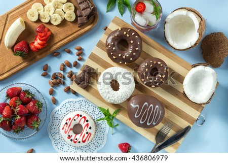 Delicious donuts. Served on the wooden board and white napkin. Decorated with strawberry, banana, coconut, mint and almond. Blue background. Horizontal image. With lemonade and ice. Top view.  - stock photo