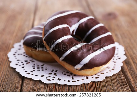 Delicious donuts with icing on lace doily on wooden background - stock photo