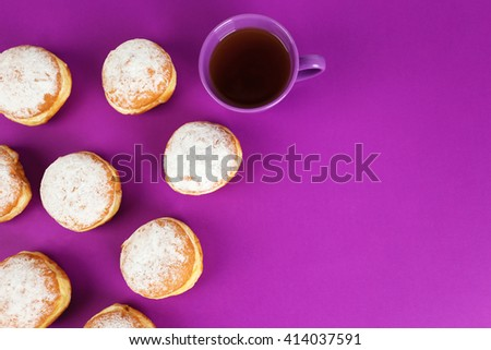 Delicious donuts with powdered sugar and cup of tea on purple surface, top view - stock photo