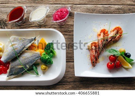Delicious dorado fish fillet on  vegetables side dish with a variety of sauces and an appetizer of tiger prawns. Lenten luxury food on wooden background - stock photo