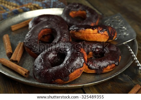 Delicious doughnuts with chocolate icing and cinnamon on metal tray close up - stock photo