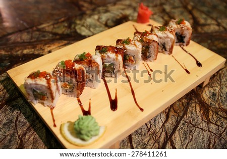 Delicious Dragon maki sushi rolls served with a wood plate. - stock photo