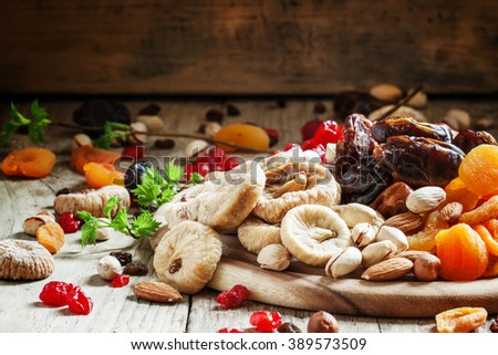 Delicious dried figs and dried fruit and nut mix on dark wooden background in rustic style, selective focus - stock photo
