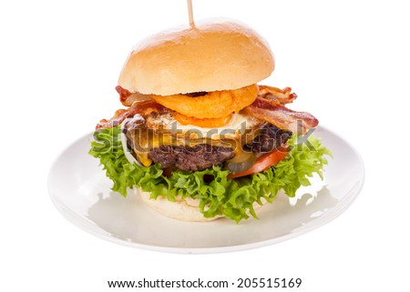 Delicious egg and bacon cheeseburger with a nutritional filling of salad ingredients, a ground beef patty, cheese, fried egg and crispy bacon on a white crusty roll