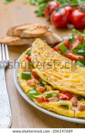 Delicious Egg Omelet with Ham and Vegetables on the Plate - stock photo
