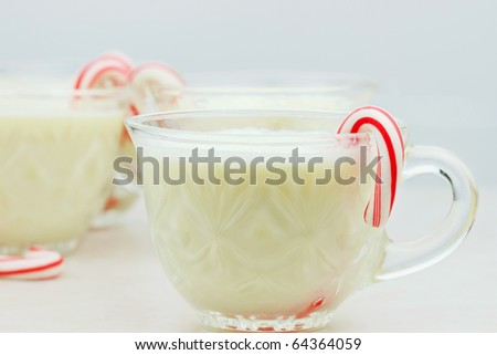 Delicious eggnog with mini candy canes. Shallow DOF with selective focus on cup in foreground.