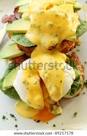 Delicious eggs benedict with hollandaise sauce with avocado with egg yolk.