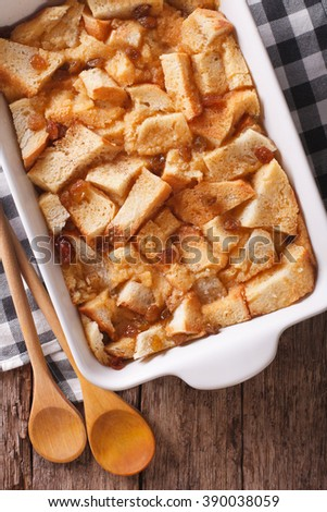 Delicious English bread pudding with raisins close up in baking dish on the table. Vertical view from above