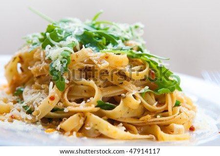 Delicious fettucine pasta with sundried tomato and rocket leaves - stock photo