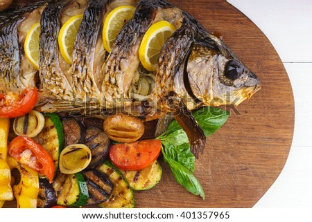 Delicious fish baked fish with lemon and condiments. Delicious roasted fish on wooden background. Grilled vegetables and baked fish on the table. - stock photo