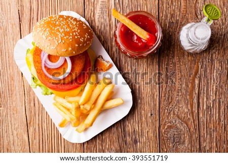 Delicious fish burgerserved with fresh french fries, servwed on a paper try.  - stock photo