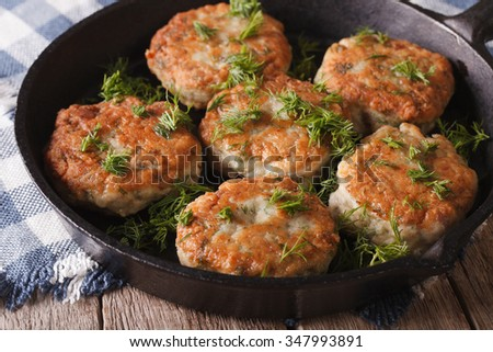 Delicious fish cakes with dill closeup in a pan on the table. Horizontal - stock photo