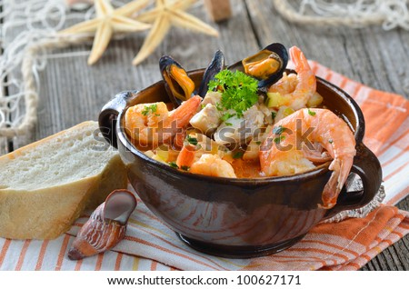Delicious fish soup with shimps, mussels, fish fillet and vegetables - stock photo