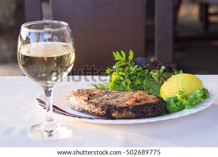 Delicious fish steak with a glass of white wine in outdoor cafe