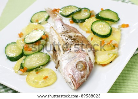 Delicious fish with vegetables served on a plate - stock photo