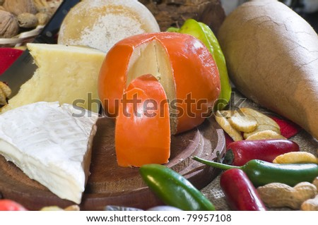 Delicious food set on a product table. Cheese, bread, nuts, vegetables. - stock photo