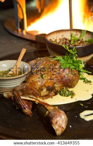 Delicious free range roasted goat shoulder served on a rustic metal plate by a hot open coal fire. Served with fresh parsley. - stock photo