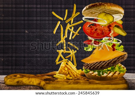 Delicious french fries and cheeseburger stacked high with a juicy beef patty, cheese, fresh lettuce, onion and tomato with flying ingredients and copyspace - stock photo