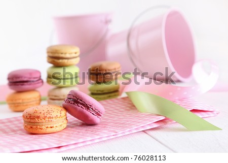 Delicious French Macaroons with ribbons on table - stock photo