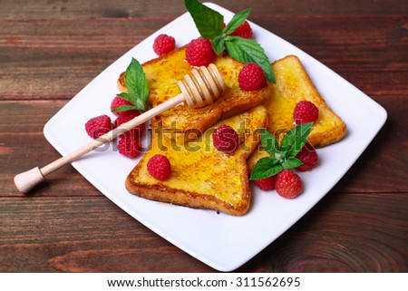 delicious French toast with raspberries and honey  - stock photo