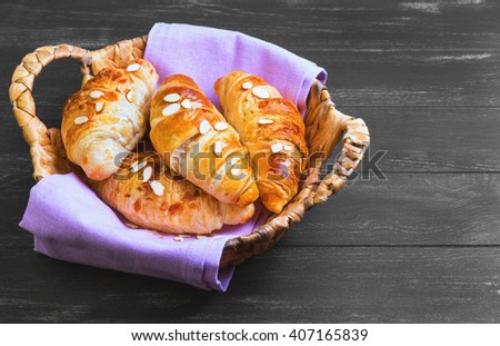 Delicious fresh almond croissants in a wicker basket with a purple cloth on a dark black wooden background in rustic style, top view, empty space for text, recipe - stock photo