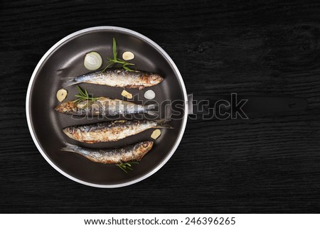 Delicious fresh anchovy fish with fresh rosemary herbs on pan on black wooden background. Culinary healthy seafood cooking. - stock photo