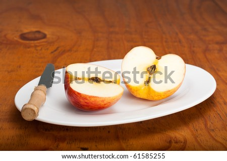 Delicious fresh apple cut in half on a white plate on a wooden table