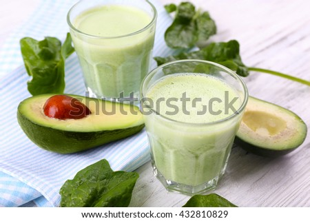 Delicious fresh avocado smoothie on white wooden background