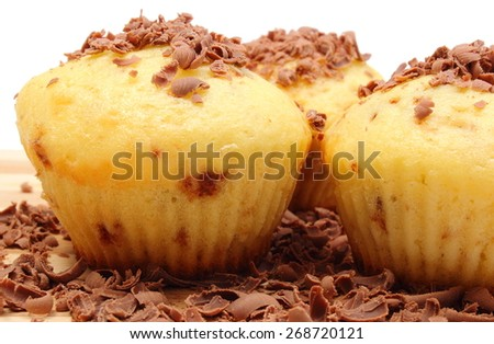 Delicious fresh baked muffins and grated chocolate lying on wooden cutting board - stock photo