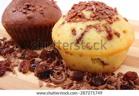 Delicious fresh baked muffins and grated chocolate with raisins lying on wooden cutting board