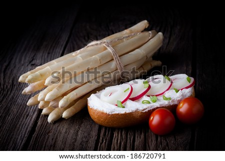Delicious fresh baked roll. Bun sandwich served with creamy cottage cheese, spring onion, red radish slices, white asparagus and tomatoes, taken on old wooden table.