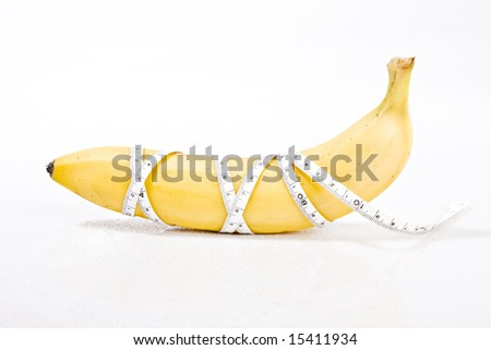 delicious fresh banana on a white surface with a measuring tape wrapped around it. concept: weight loss, diet - stock photo