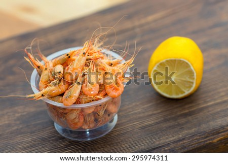 Delicious fresh cooked shrimp prepared to eat. Cooked shrimps with lemon on wooden table. Snack to beer and wine. Shrimp from the Black Sea. Serve cooked shrimp and lemon on a bar table. - stock photo