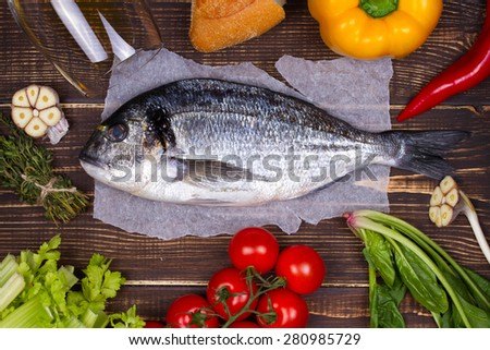 Delicious fresh fish and vegetables on dark vintage background - stock photo