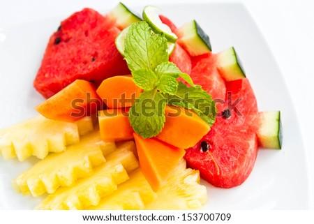 Delicious fresh fruit on white plate - stock photo