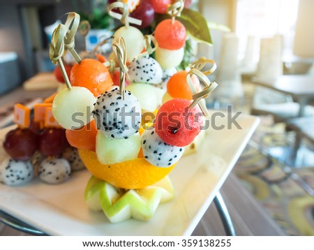 Delicious fresh fruit salad balls in orange bowl. Beautifully decorated catering banquet table in restaurant or cafe. - stock photo